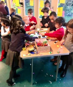A group of children standing around a craft table and participating in Designing My Happy City: Playground.
