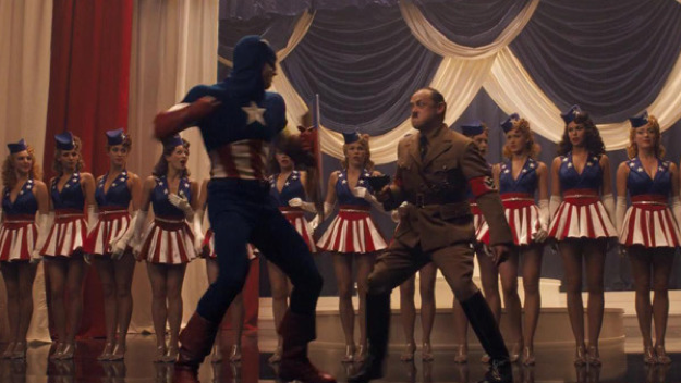 Picture of a scene from the film 'Captain America: The First Avenger'. Captain America stands on a stage in front of a person acting as Adolf Hitler. Captain America pretends to punch him.