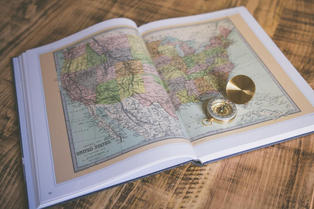 A book lies open on a wooden table, turned to map of the United States of America that spans two pages. A golden compass sits open on the right-hand page.