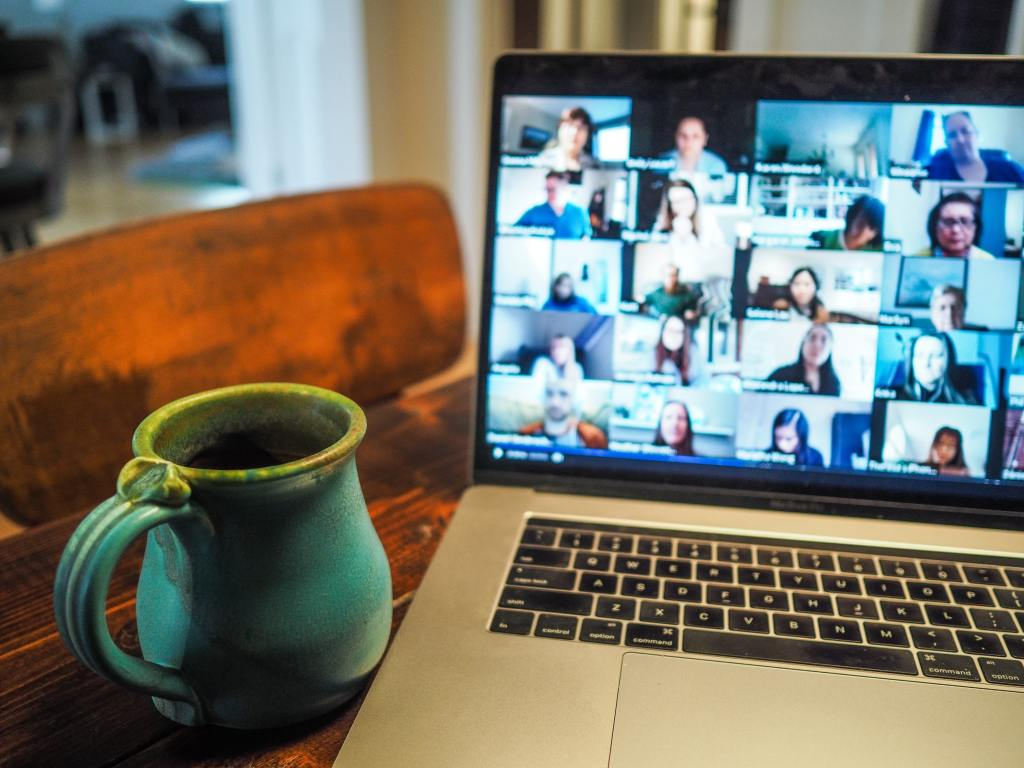 A laptop on a table next to a blue/green ceramic mug. On the laptop screen is a Zoom conference of some sort.