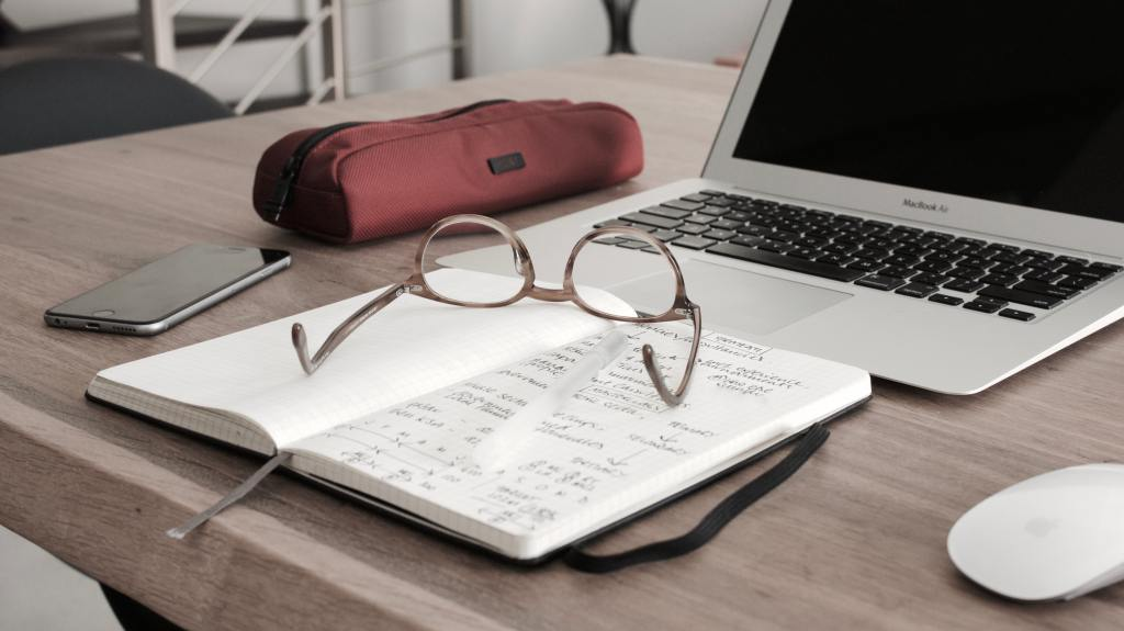 A laptop on a table next to a red pencil bag, a smart phone and a journal that is lying open with a pair of glasses sitting on top. The laptop screen is blank.