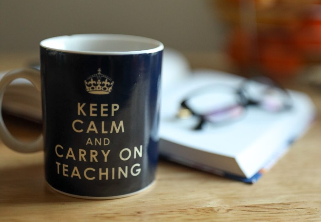 A blue mug that has an icon of a crown and says 'Keep Calm and Carry On Teaching' sits in front of an open book. A pair of glass sits on top of the book.