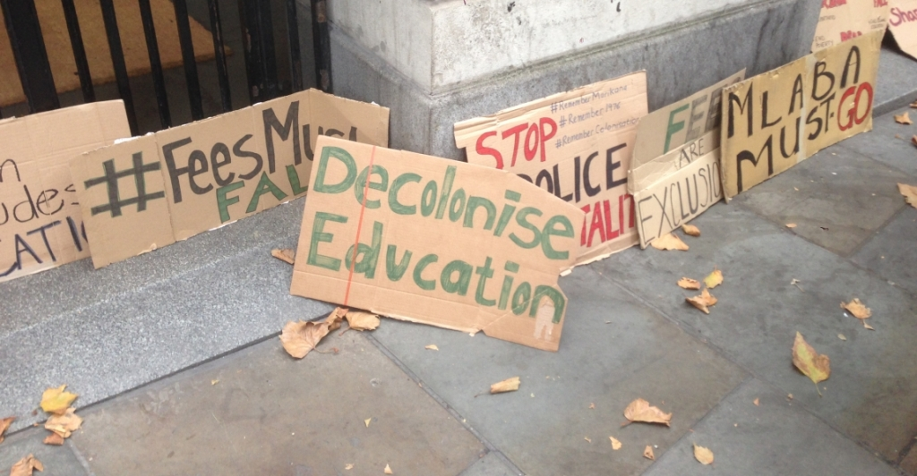 Various cardboard signs from a student protest, some calling for decolonisation.