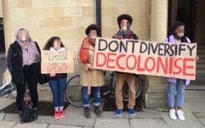 Students at a protest at the University of Glasgow holding signs that say 'Will you listen when we speak?' and 'Don't Diversify, Decolonise'.