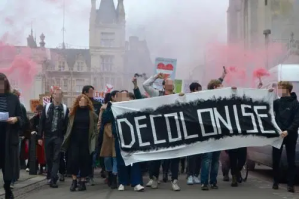 Students at a protest in Glasgow holding a large banner that says 'Decolonise'.