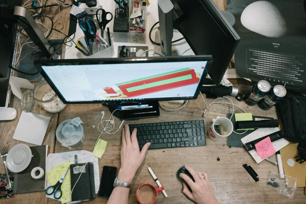 A messy desk, with items crowding the work area.