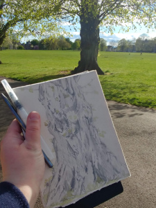 The photographer holds their journal up in front of the camera with a drawing of the tree in the distance on the journal page.