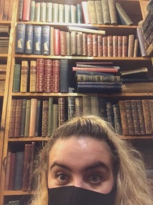 A selfie of the author of the post, Shelby, masked and standing in front of a bookshelf lined with old books.