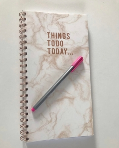 A pink and white marbelized journal with the words 'Things To Do Today . . .' written on the cover. A pink and silver pen lies across it.