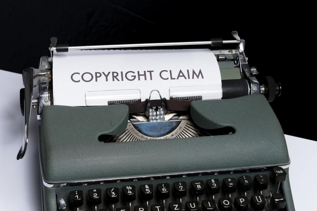 A grey typewriter sitting on a table. The paper inside the typewriter says 'COPYRIGHT CLAIM'.