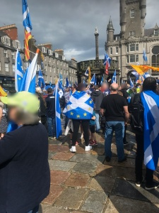 A supporter of Scottish independence is wrapped in a flag which blends the saltire and European stars at a pro-independence march in Aberdeen, August 2019.