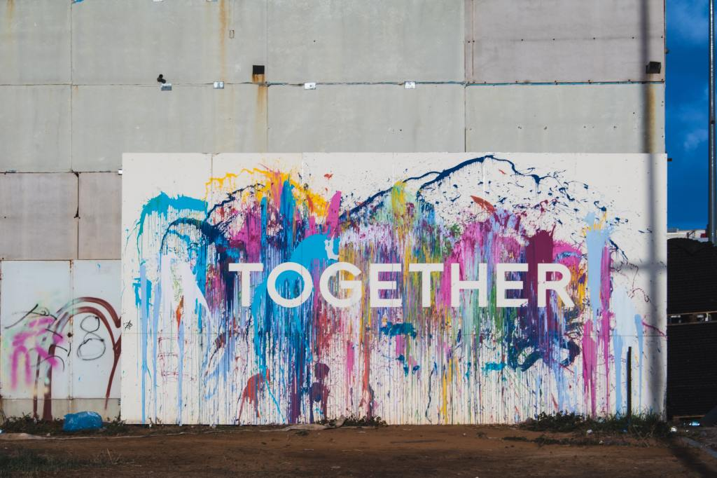 Multiple colours of paint are splatter against a white backdrop in front of a building. In the middle of the splash, the word 'TOGETHER' is in white.
